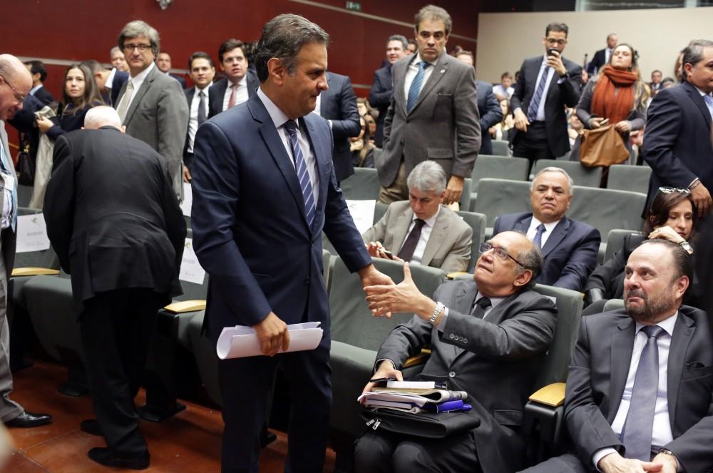 Ministro Gilmar Mendes cumprimenta Senador Aécio Neves durante conferência em Lisboa, em 31 de março de 2016.