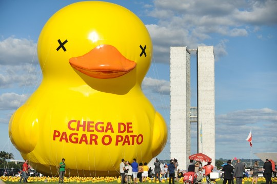 """The Federation of Industries of the State of Sao Paulo (FIESP) protest with a giant duck against taxes with a giant duck with an inscription that reads """"Enough of taking the blame"""" at the Esplanada dos Ministérios in Brasilia on March 29, 2016. AFP PHOTO/ANDRESSA ANHOLETE / AFP / Andressa Anholete        (Photo credit should read ANDRESSA ANHOLETE/AFP/Getty Images)"""