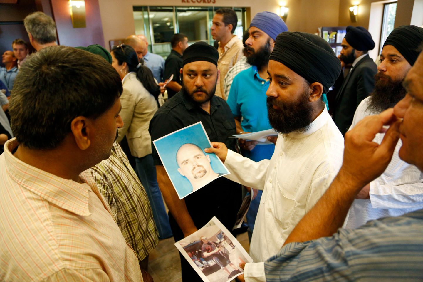 OAK CREEK, WI - AUGUST 6: Members of the community hold up the mug shot handed out by the FBI of the suspected shooter Wade Michael Page after a press conference on the shooting at the Sikh Temple of Wisconsin where yesterday a gunman fired upon people at service August, 6, 2012 in Oak Creek, Wisconsin. At least six people were killed when the shooter identified as Wade Michael Page opened fire on congregants in the Milwaukee suburb. The suspect who was a United States Army veteran was killed in a shootout with  police.  (Photo by Darren Hauck/Getty Images)