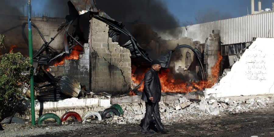 A Yemeni man walks past flames rising from the ruins of buildings destroyed in a Saudi-led airstrike on Feb. 10, 2016 in Sanaa.