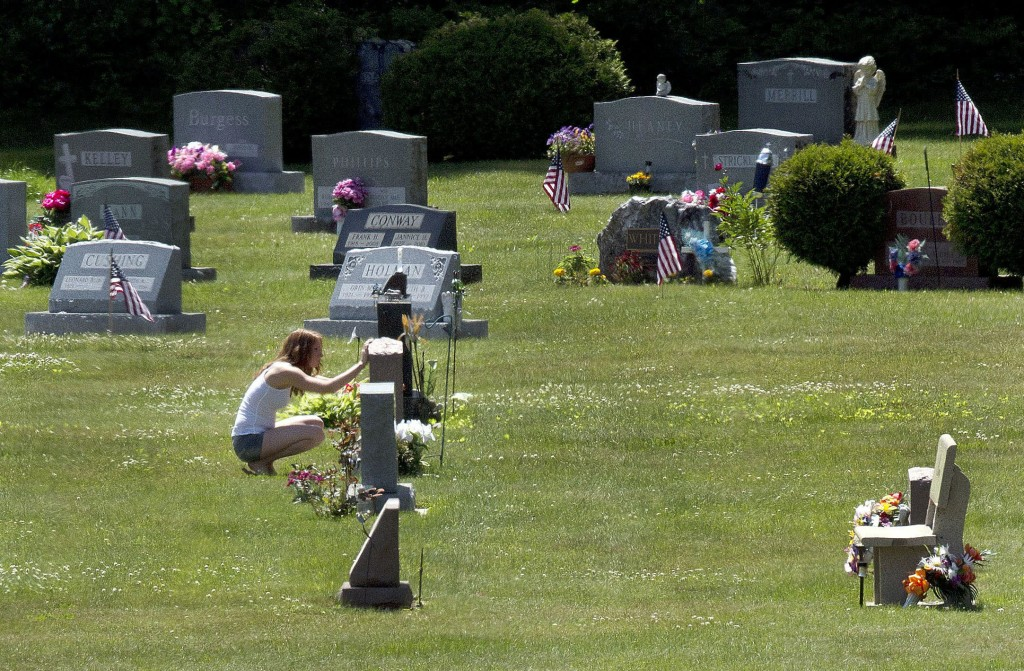 FILE - In this June 17, 2016 file photo, Erika Marble visits the gravesite of Edward Martin III, her fiancé and father of her two children, in Littleton, N.H. The 28-year old died Nov. 30, 2014, from an overdose of the opioid Fentanyl. Drug overdose deaths increased by 33 percent in the past five years across the U.S. as of 2016. New Hampshire saw a 191 percent increase while Massachusetts, North Dakota, Connecticut and Maine saw death rates jump by more than 100 percent.(AP Photo/Jim Cole, File)