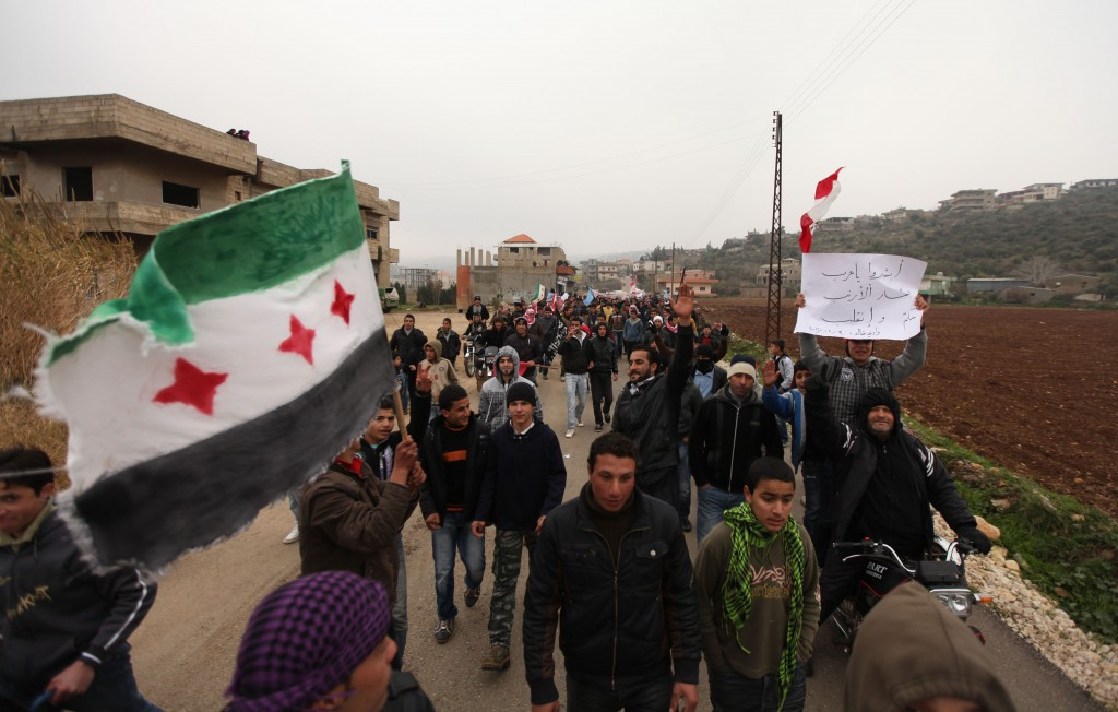 Demonstrators take to the streets of Wadi Khaled, on the Lebanese-Syrian border, during the Crawling Friday protest against the Syrian regime on December 30, 2011, waving Syria's old national flag (L) and a placard mocking President Bashar al-Assad. AFP PHOTO/SI MITCHELL (Photo credit should read Si Mitchell/AFP/Getty Images)