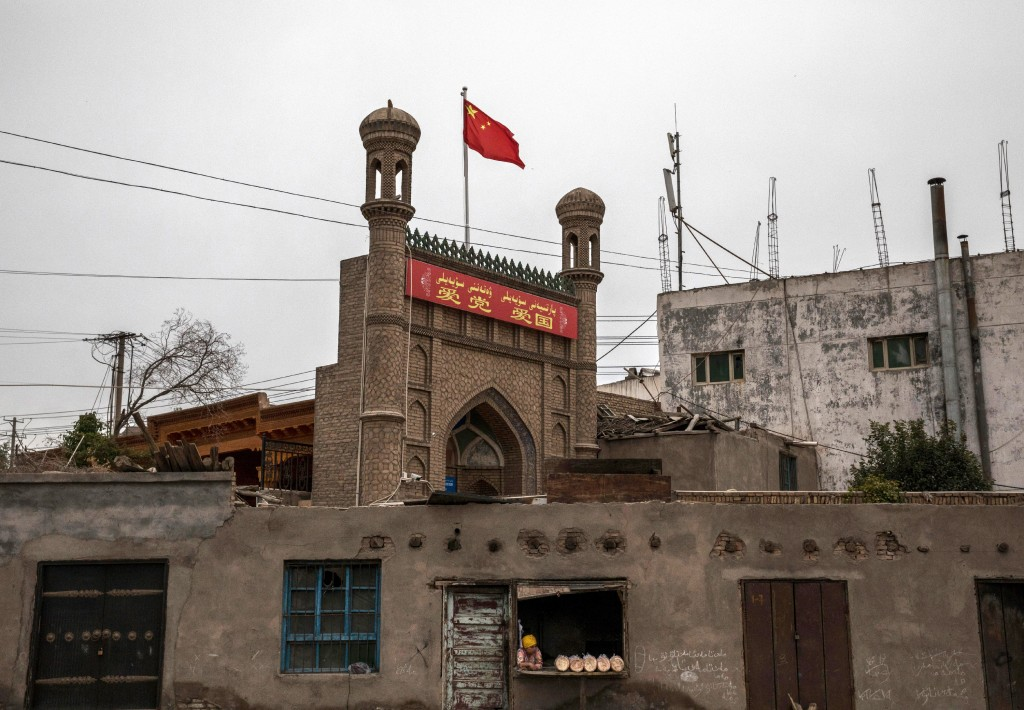 KASHGAR, CHINA - JUNE 28: A Chinese flag flies over a local mosque recently closed by authorities as an ethnic Uyghur woman sells bread at her bakery on June 28, 2017 in the old town of Kashgar, in the far western Xinjiang province, China. Kashgar has long been considered the cultural heart of Xinjiang for the province's nearly 10 million Muslim Uyghurs. At an historic crossroads linking China to Asia, the Middle East, and Europe, the city has changed under Chinese rule with government development, unofficial Han Chinese settlement to the western province, and restrictions imposed by the Communist Party. Beijing says it regards Kashgar's development as an improvement to the local economy, but many Uyghurs consider it a threat that is eroding their language, traditions, and cultural identity. The friction has fuelled a separatist movement that has sometimes turned violent, triggering a crackdown on what China's government considers 'terrorist acts' by religious extremists. Tension has increased with stepped up security in the city and the enforcement of measures including restrictions at mosques. (Photo by Kevin Frayer/Getty Images)