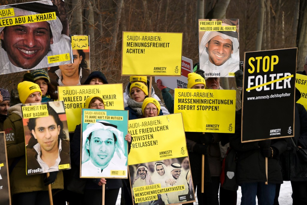 Members of Human rights NGO Amnesty International hold giant portraits of jailed Saudi blogger Raif Badawi and Saudi rights activist and lawyer Waleed Abu Alkhair as they demonstrate in front of the Embassy of Saudi Arabia in Berlin, on January 8, 2016 to ask for their release. Badawi was sentenced to 10 years in prison and 1,000 lashes for insulting Islam. / AFP / TOBIAS SCHWARZ (Photo credit should read TOBIAS SCHWARZ/AFP/Getty Images)