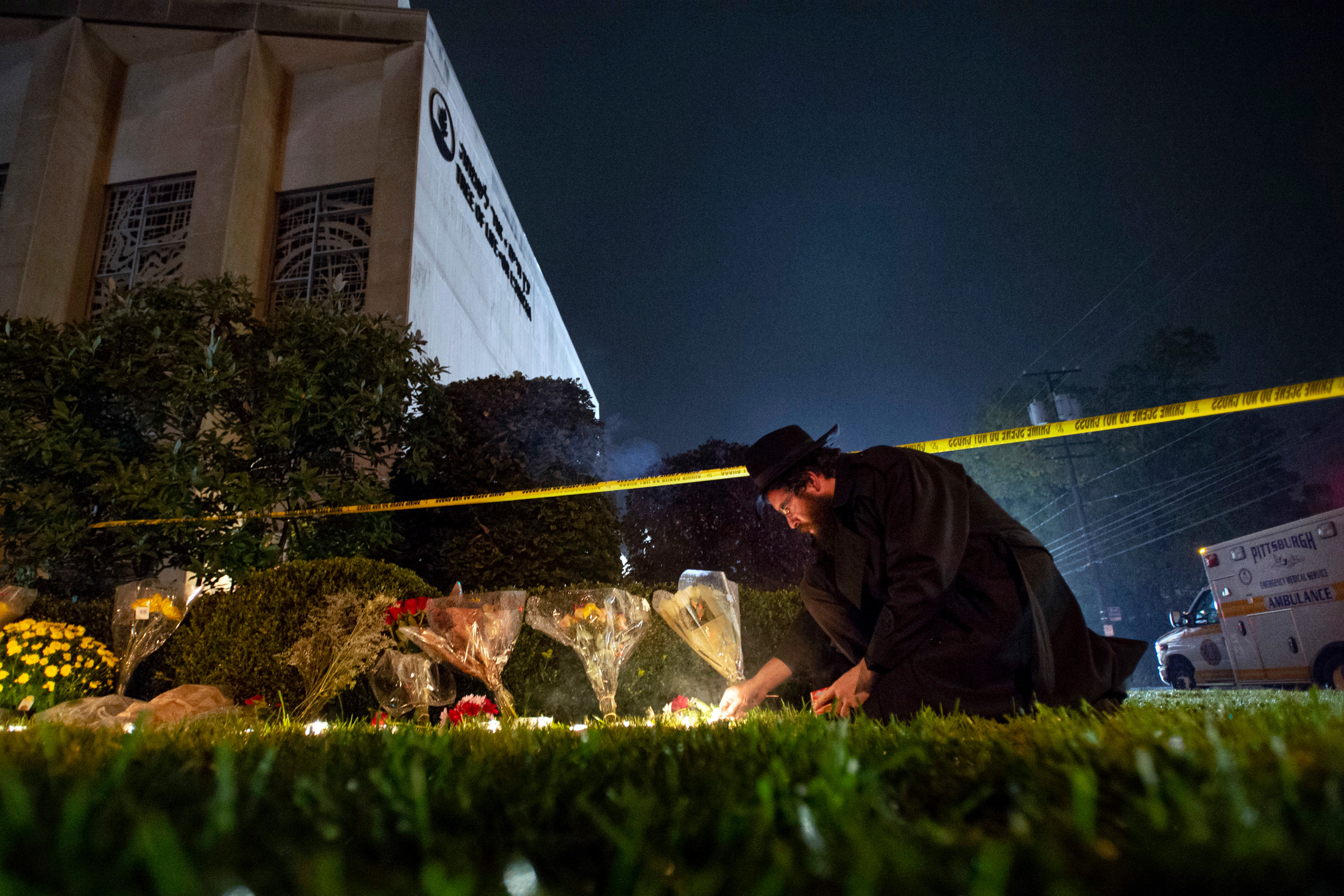 In this Oct. 27, 2018 photo, Rabbi Eli Wilansky lights a candle after a mass shooting at Tree of Life  Synagogue in Pittsburgh's Squirrel Hill neighborhood. Robert Bowers, the suspect in Saturday's mass shooting, expressed hatred of Jews during the rampage and told officers afterward that Jews were committing genocide and he wanted them all to die, according to charging documents made public Sunday. (Steph Chambers/Pittsburgh Post-Gazette via AP)