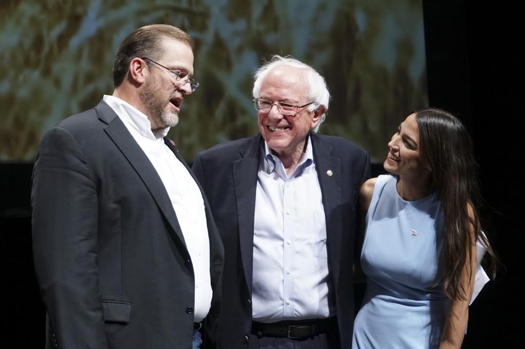 James Thompson, candidato do Partido Democrata ao Congresso pelo Kansas, à esquerda; Senador Bernie Sanders, Independente por Vermont; e Alexandria Ocasio-Cortez, candidata do Partido Democrata ao Congresso por Nova York se reúnem no palco depois de um comício em Wichita, no Kansas, em 20 de julho de 2018.