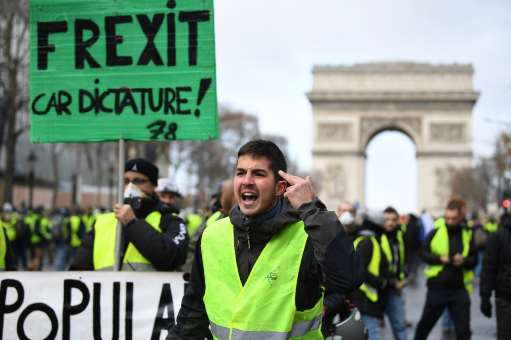 "PARIS, FRANCE - DECEMBER 08: A demonstrator gestures in front of placards, one of which says 'Frexit car dictature!' during the demonstration of the yellow vests at the Arc de Triomphe on December 08, 2018 in Paris France. 'Yellow Vests' (""Gilet Jaunes"" or ""Vestes Jaunes"") is a protest movement without political affiliation that protests against taxes and rising fuel prices. The ""Yellow Vest"" protests have wrecked parts of Paris and other French cities for nearly a month, as the movement - inspired by opposition to a new fuel tax - has absorbed a wide range of anti-government sentiment. (Photo by Jeff J Mitchell/Getty Images)"
