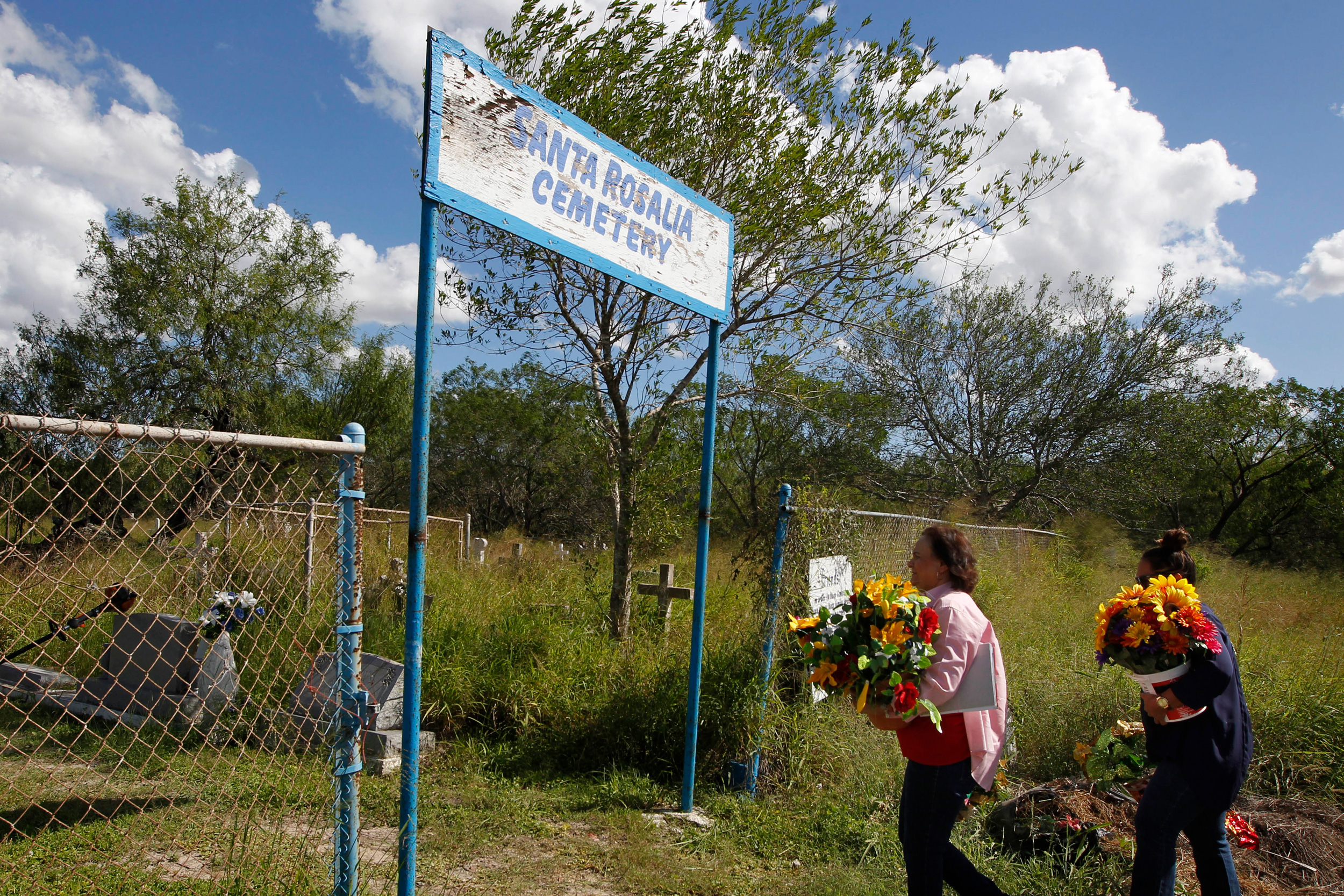 Estela Aguilar Hernandez, left, and her daughter Cecilia Hernandez carry flowers for the graves of deceased relatives into the Santa Rosalia Cemetery on Tuesday, Oct. 24, 2017, in Brownsville, Texas. Hernandez' grandparents and many other relatives are buried at the cemetery, which is located south of the border wall just north of the Rio Grande. Hernandez fears last year's approval of border gate funding will limit access to the cemetery.  (Nathan Lambrecht/The Monitor via AP)