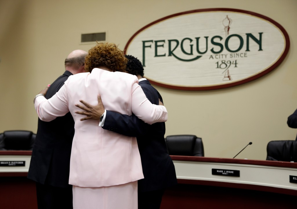 Three newly elected members of the Ferguson City Council, from left, Brian Fletcher, Ella Jones and Wesley Bell embrace after being sworn in during a monthly meeting of the council Tuesday, April 21, 2015, in Ferguson, Mo. With the election, half of the six-member city council in Ferguson, a town where two-thirds of the 21,000 residents are black, will now be African-American. (AP Photo/Jeff Roberson)