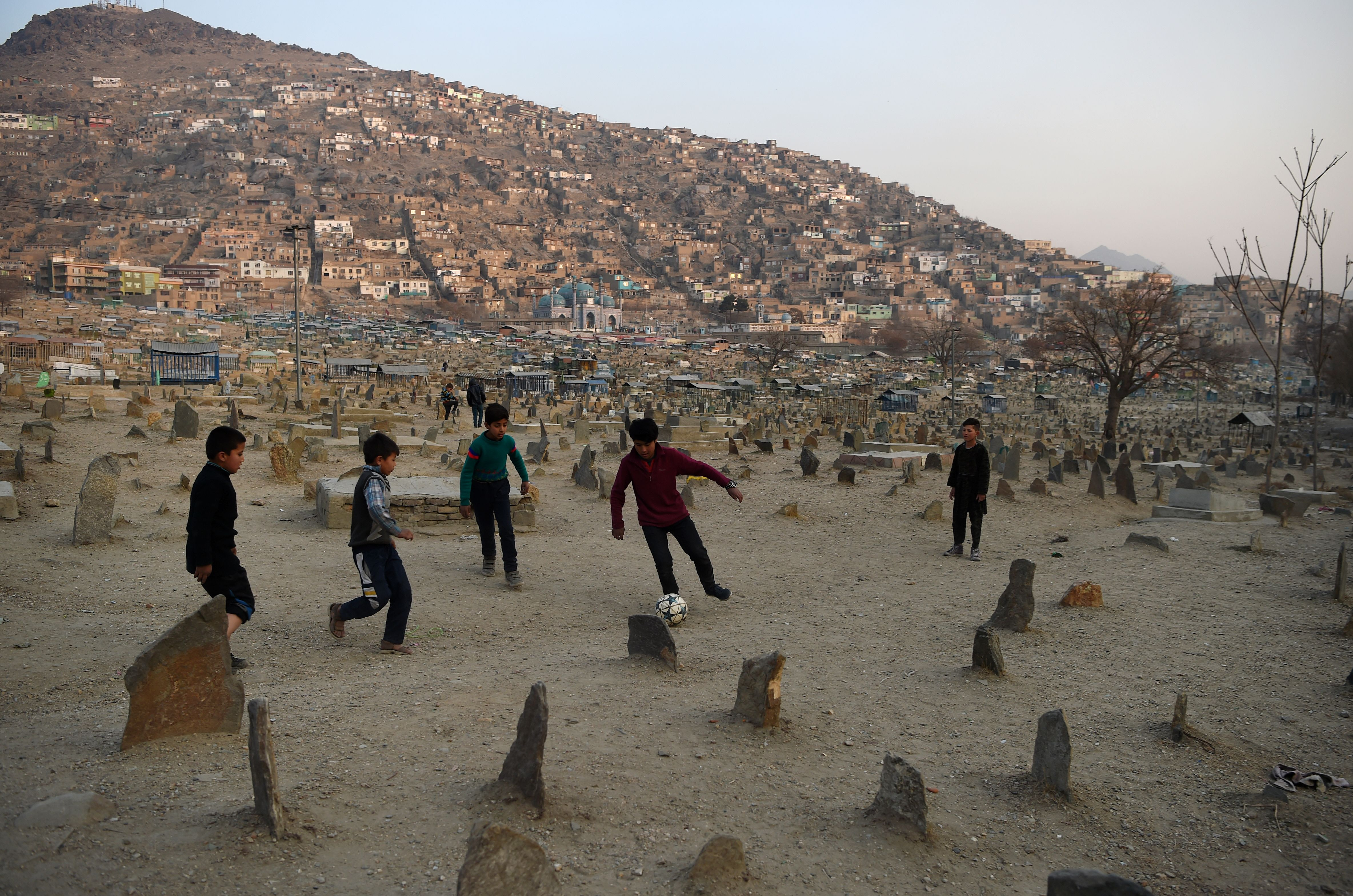 Afghan boys play football at at the Kart-e-Sakhi cemetery in Kabul on December 30, 2018. (Photo by WAKIL KOHSAR / AFP) (Photo credit should read WAKIL KOHSAR/AFP/Getty Images)