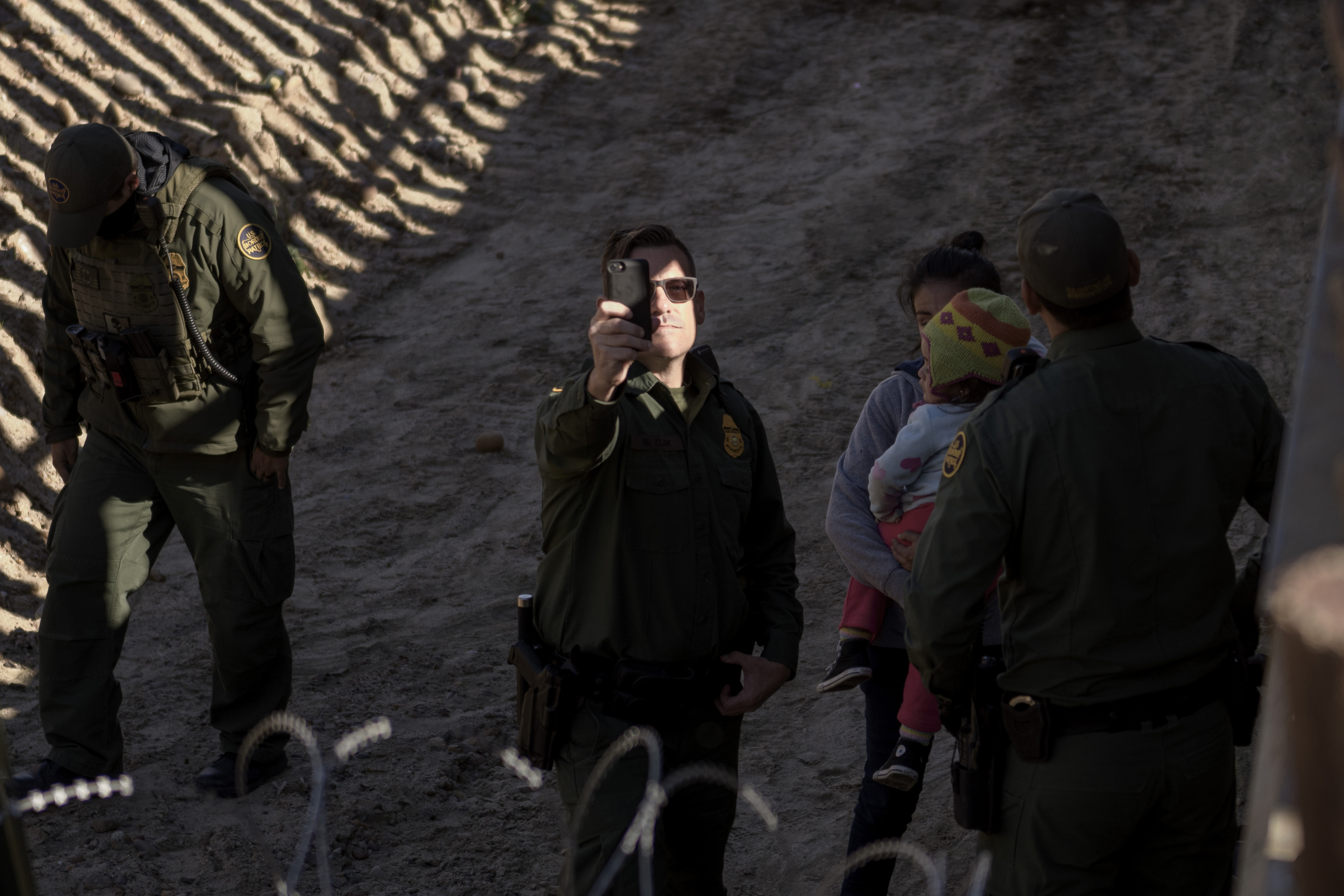 A Border Patrol officers uses his cell phone to take snapshots of the journalists after a Mexican migrant with her daughter jumped the border fence to get into the U.S. side to San Diego, Calif., from Tijuana, Mexico, Saturday, Dec. 29, 2018. Discouraged by the long wait to apply for asylum through official ports of entry, many migrants from recent caravans are choosing to cross the U.S. border wall and hand themselves in to border patrol agents. (AP Photo/Daniel Ochoa de Olza)