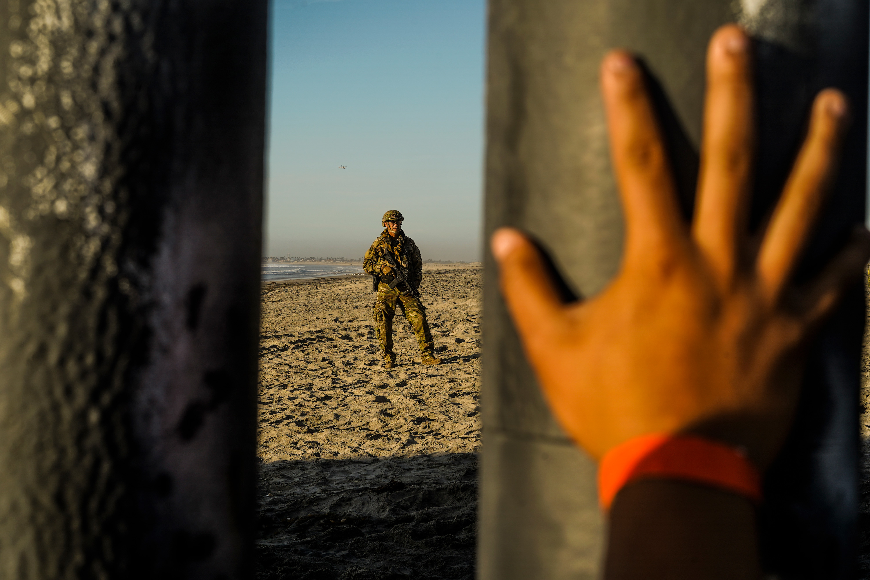 A soldier is seen on the US side of the border fence while a Honduran migrant's hand is placed on the border fence on Mexico side in Tijuana, Mexico on November 16, 2018.Thousands of Central American migrants, who are trying to go to the US, arrived in the US/Mexico border town of Tijuana in mid November 2018 however most of them have hard time to find a way to cross the border to the US. Go Nakamura