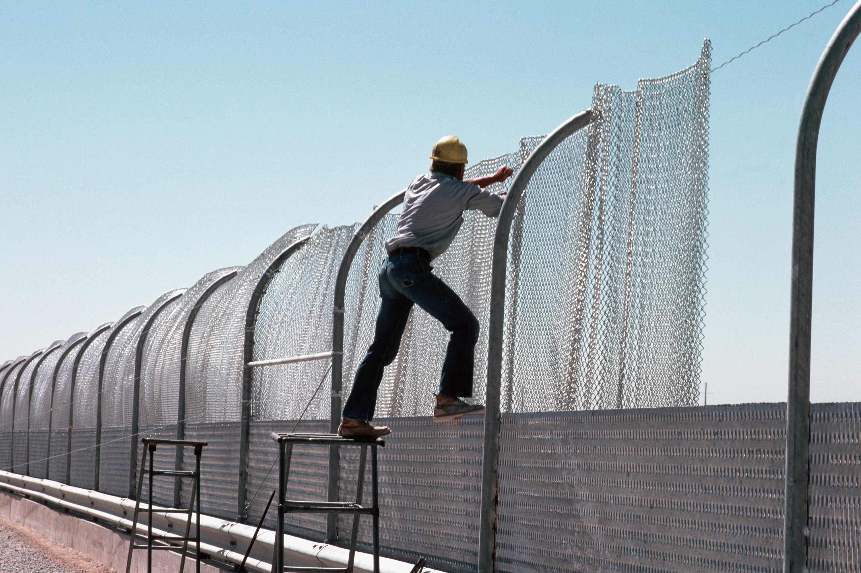 "A construction worker pulls steel mesh into place on a section of the galvanized steel fence being built along the border between the United States and Mexico in 1979. The fence, intended to keep illegal aliens from crossing into the US, is known as the ""Tortilla Curtain."" (Photo by © Stephanie Maze/CORBIS/Corbis via Getty Images)"