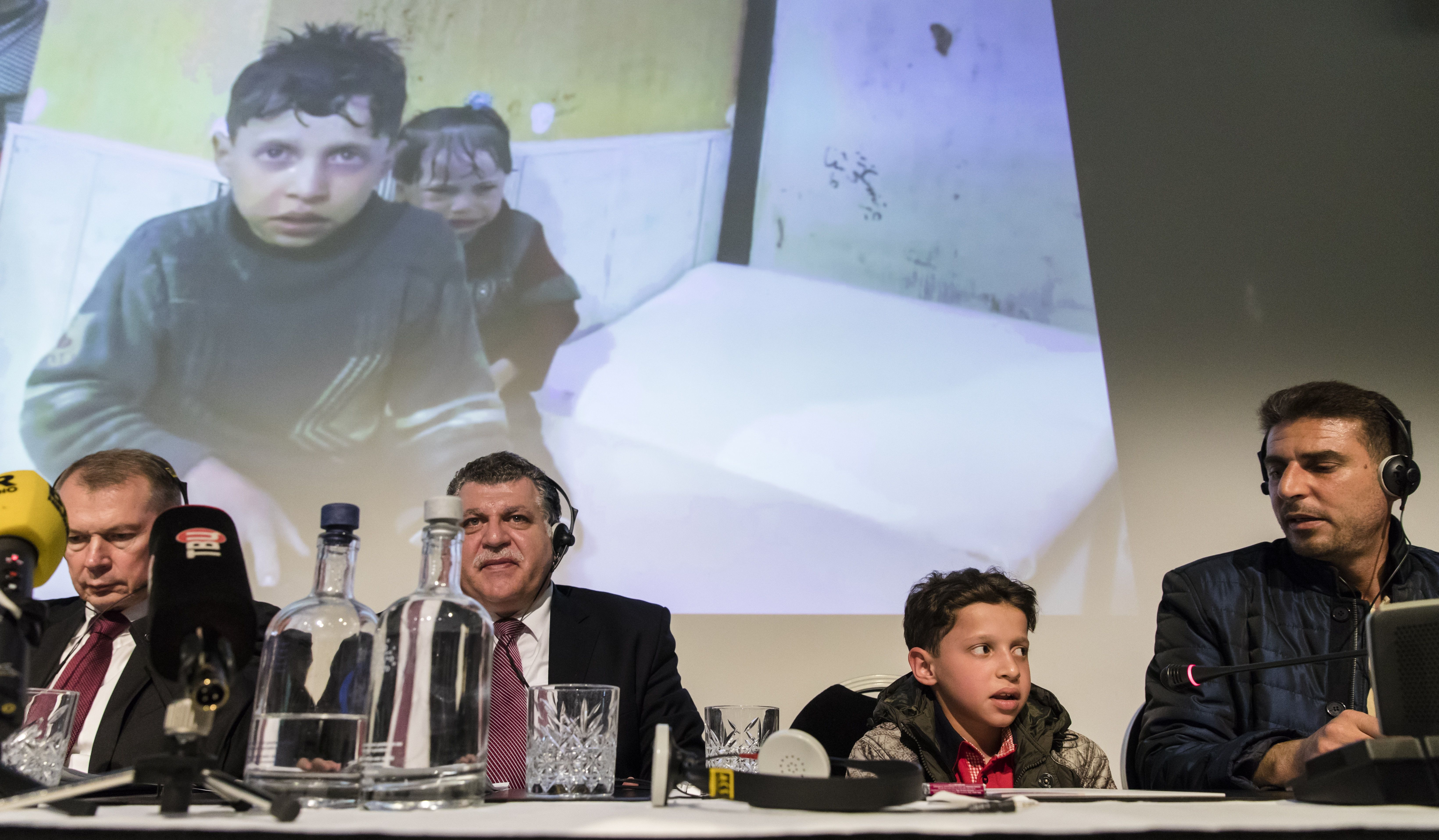 "(From L) Russian ambassador in The Netherlands Aleksander Shulgin (L), Syrian deputy representative at the Organisation for the Prohibition of Chemical Weapons (OPCW) Ghassan Obaid, a Syrian boy (appearing on the video above) and a Syrian man attend a press conference in The Hague on April 26, 2018 called by Russian embassy to present what it says are witnesses 'used to stage' Douma attack videos. - Russian diplomats said they are organising the briefing for OPCW member nations and would ""bring some Syrians to speak about the reported Douma incident"". The Russian embassy in the Netherlands said in a tweet that the briefing would involve ""witnesses from Syria who were at the staged videos of #WhiteHelmets"" -- a humanitarian organisation made up of some 3,000 volunteers working in rebel-held areas. On April 7, the Syrian American Medical Society (SAMS) and the White Helmets jointly said dozens of people died in a ""poisonous chlorine gas attack"" in Douma. The OPCW said it had urged the Russian delegation to allow its experts to interview the witnesses first, and to hold the briefing ""once the FFM has completed its work"". ""Nevertheless, the Russian delegation stated that it would go ahead with the briefing and that its intention was not to interfere with the FFMs work,"" the OPCW statement added. (Photo by Bart MAAT / ANP / AFP) / Netherlands OUT        (Photo credit should read BART MAAT/AFP/Getty Images)"