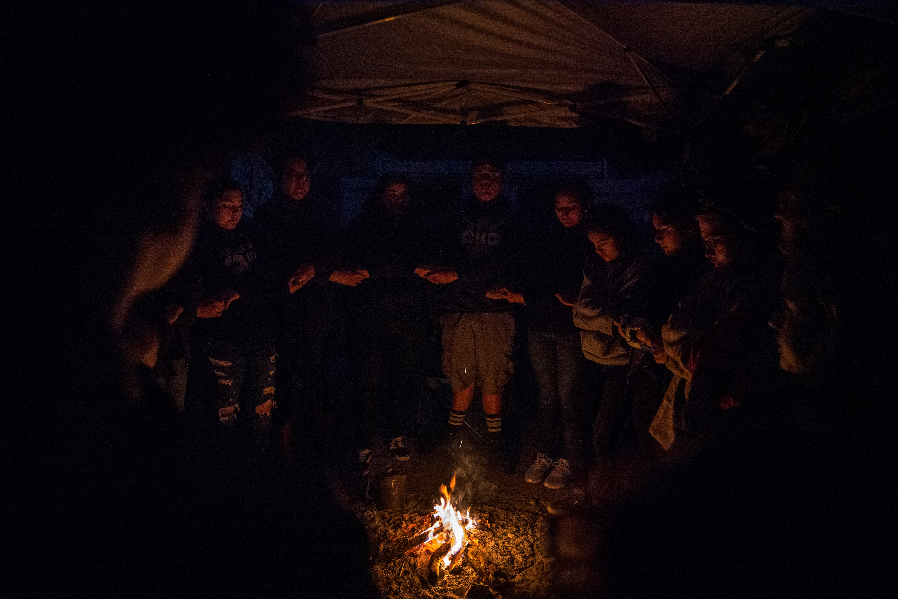 """""""Al Exito"""" members along with Carrizo/Comecrudo Tribe members, and activists gather around the fire to share things that they are thankful for at Yalui Village in Hidalgo County, Texas on March 17, 2019.Photo: Verónica G. Cárdenas for The Intercept"""