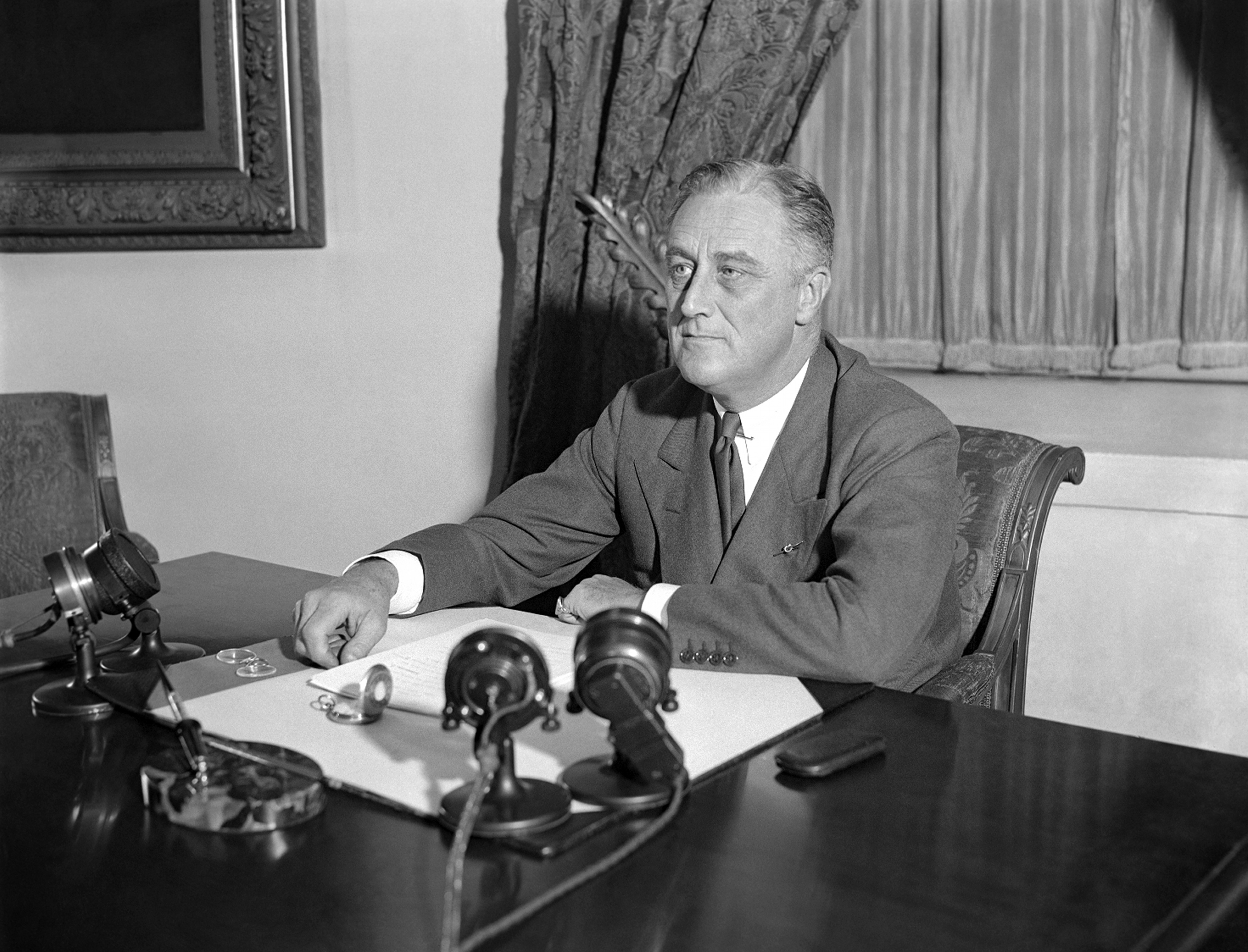 FILE - In this May 7, 1933, file photo, President Franklin D. Roosevelt is shown at his desk at the White House, in Washington, when he outlined his ideas to the nation on a partnership between the government and agriculture, industry, and transportation. He announced measures to be proposed soon to give industrial workers a better deal. A president's first 100 days can be a tire-squealing roar from the starting line, a triumph of style over substance, a taste of what's to come or an ambitious plan of action that gets rudely interrupted by world events. (AP Photo)