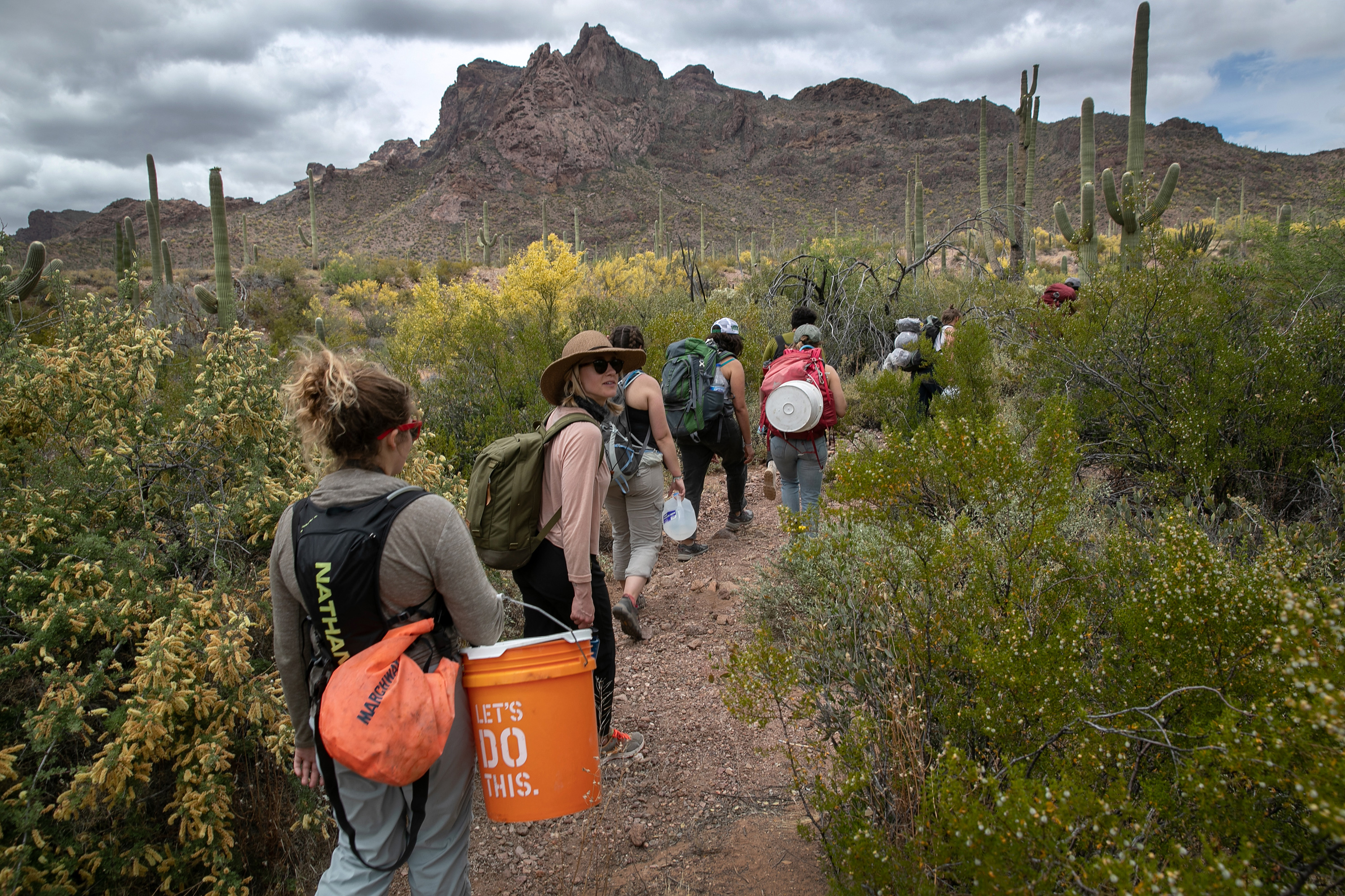 AJO, ARIZONA - MAY 10: Volunteers for the humanitarian aid organization No More Deaths walk with buckets of food and jugs of water for undocumented immigrants on May 10, 2019 near Ajo, Arizona. The volunteers distributed the aid along trails in remote areas where immigrants pass after crossing the border from Mexico. The number of immigrant deaths, mostly due to dehydration and exposure, has risen as higher border security in urban border areas has pushed immigrant crossing routes into more remote desert regions. No More Deaths volunteer Scott Warren is scheduled to appear in federal court on May 29 in Tucson, charged by the U.S. government on two counts of harboring and one count of conspiracy for aiding two Central American immigrants in January, 2018. If found guilty Warren could face up to 20 years in prison. The trial is seen as a watershed case by the Trump Administration, as it pressures humanitarian organizations working to reduce suffering and deaths of immigrants in remote areas along the border. The government claims the aid encourages human smuggling. In a separate misdemeanor case, federal prosecutors have charged Warren with public littering, for distributing food and water along migrant trails. (Photo by John Moore/Getty Images)