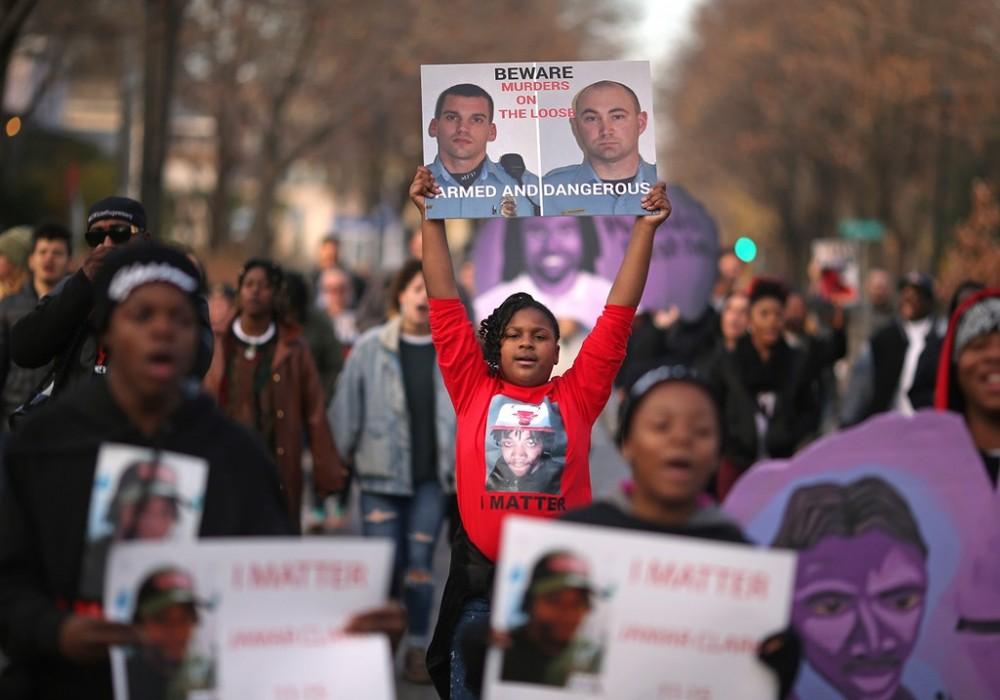 Uma sobrinha de Jamar Clark exibe as fotos de dois policiais de Minneapolis que se envolveram na morte de seu tio, em protesto ocorrido na cidade em 15 de outubro de 2016.