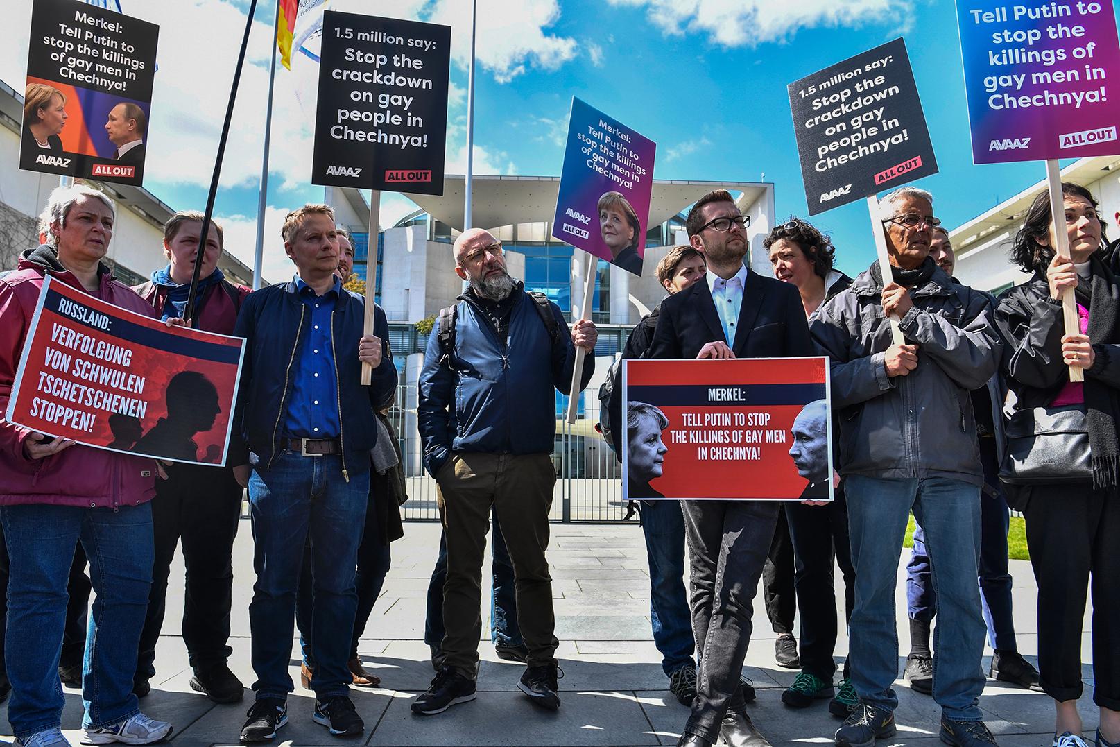 Ativistas exibem cartazes diante da Chancelaria de Berlim em 30 de abril de 2017, durante uma manifestação exigindo do presidente da Rússia o fim da perseguição aos homens gays na Chechênia.