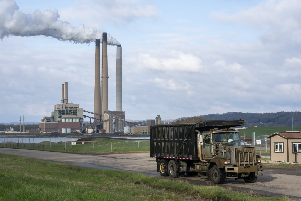 A truck carts coal ash as emissions rise from a smoke stack at the Conesville Power Plant in Conesville, Ohio, U.S., on April 18, 2020.