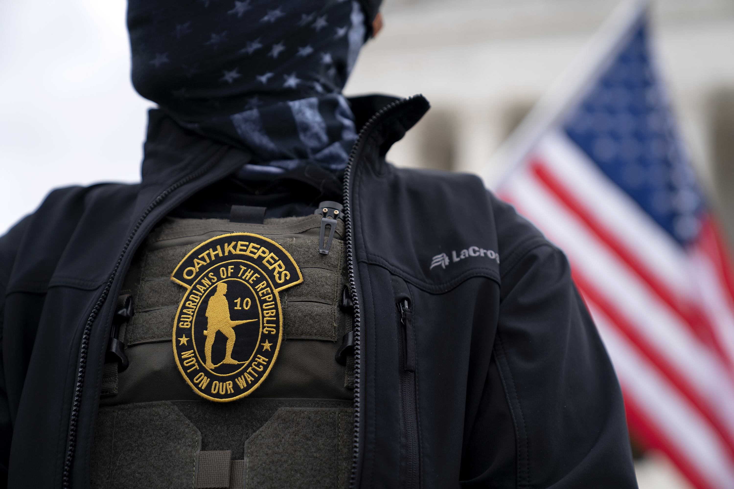 A demonstrator wears an OathKeepers anti-government organization badge on a protective vest during a protest outside the Supreme Court in Washington, D.C., U.S., on Tuesday, Jan. 5, 2021. Republican lawmakers in Washington are fracturing over President Trump's futile effort to persuade Congress to overturn his re-election defeat, as his allies spar with conservatives who say the Constitution doesn't give them the power to override voters. Photographer: Stefani Reynolds/Bloomberg via Getty Images