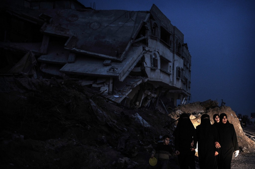 Palestinian women and a child walk past a destroyed house in the Israeli-bombed Jabalia in the northern Gaza Strip on January 23, 2009. A Hamas delegation from Gaza crossed into Egypt for talks to shore up the ceasefire with Israel which ended a 22-day assault on the coastal strip, a border official said. Israel and Hamas have observed their own ceasefires since January 18 when Israel ended Operation Cast Lead leaving a trail of devastation and 1,330 Palestinians dead, according to doctors. Egypt is trying to secure a durable ceasefire between Israel and Hamas and the reopening of crossings. AFP PHOTO/OLIVIER LABAN-MATTEI (Photo credit should read OLIVIER LABAN-MATTEI/AFP via Getty Images)