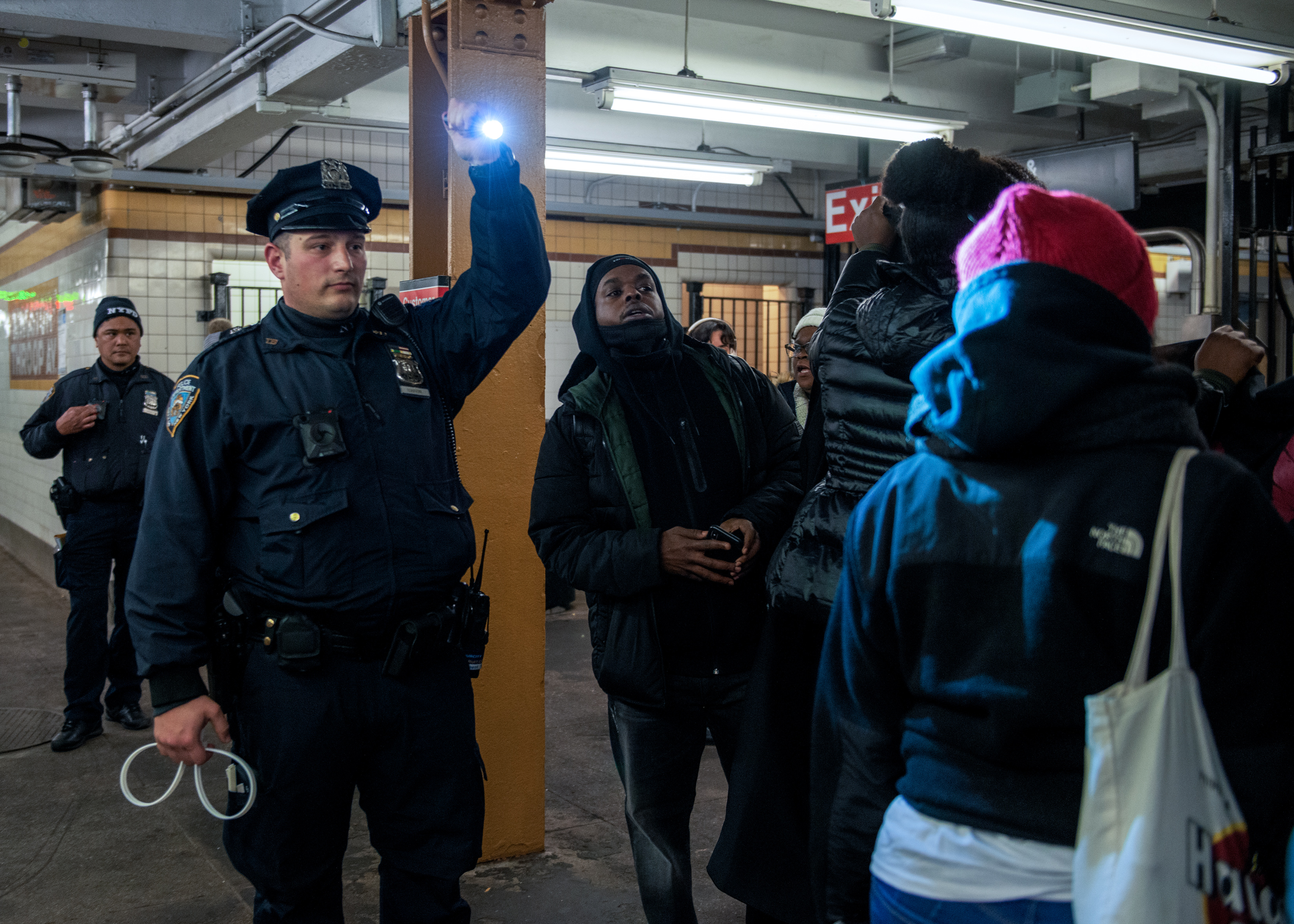 A police officer shines a flashlight on protesters as they exit the subway on January 31, 2020. The protest was in response to increased police presence in New York City subways. Police claim that they need to step up their fare evasion enforcement, and that fare evaders cost the transit agency $240 million a year. Activists, however, see the additional police presence as a war on poor people. (Photo by Aidan Loughran/NurPhoto via Getty Images)