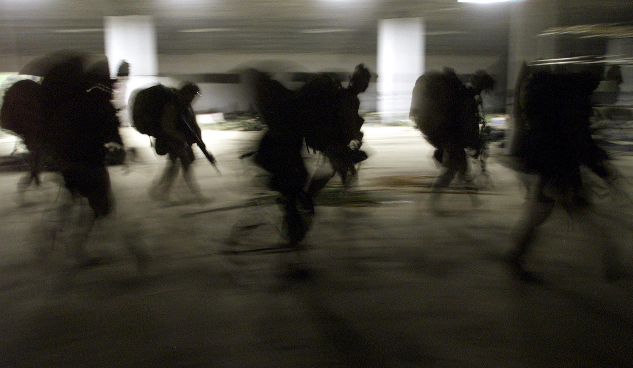 In this file photo taken on November 29, 2001 United States Marines from Bravo Co. of the 15th MEU (Marine Expeditionary Unity) march into the barracks in full battle gear as they arrive very early morning at the US Marines forward base in southern Afghanistan. - Launched in the wake of the September 11 attacks, the war in Afghanistan claimed the lives of tens of thousands of Afghans along with around 2,400 US soldiers and saw trillions squandered in what has largely been deemed a failed nation-building project. (Photo by JIM HOLLANDER / POOL / AFP) (Photo by JIM HOLLANDER/POOL/AFP via Getty Images)